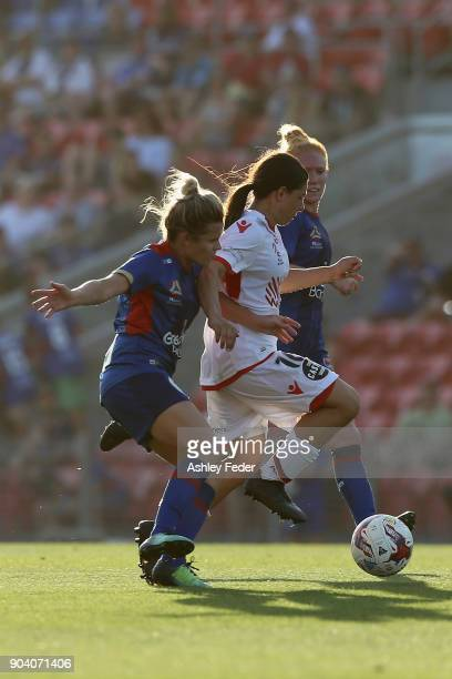 Alexandra Chidiac of Adelaide United runs the ball ahead of Cassidy Davis and Victoria Huster during the round 11 WLeague match between the Newcastle...