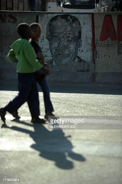 Alexandra children walk past an old painiting of Nelson Mandela on the street of Alexandra township on June 27, 2013. Mandela is spending his 20 day...