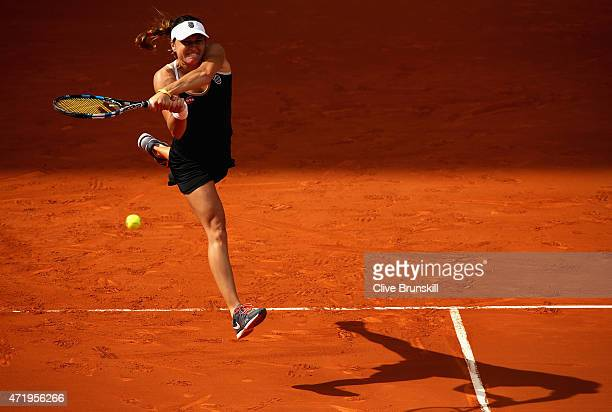Alexandra Dulgheru of Romania leaps to play a backhand against Ana Ivanovic of Serbia in their first round match during day one of the Mutua Madrid...