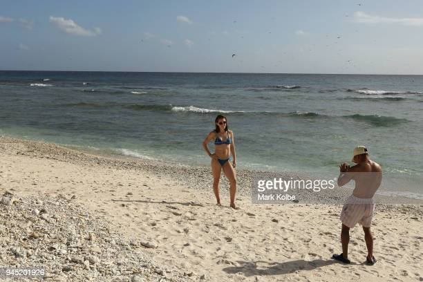 Alexandra Eade of Australia poses on the beach as Chris Remkes of Australia take her picture during an athletes Great Barrier Reef experience as part...