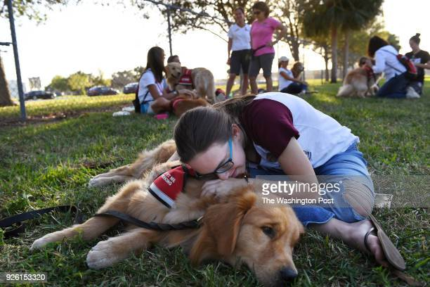 Alexandra Geisser embraces a therapy dog named Mickey outside Marjory Stoneman Douglas High School as students and family members take part in an...
