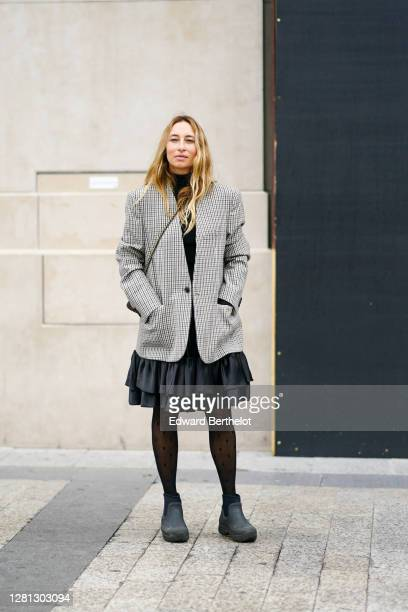 Alexandra Golovanoff wears a black turtleneck pullover a gray checkered blazer jacket a black ruffled pleated skirt tights shoes outside Miu Miu...