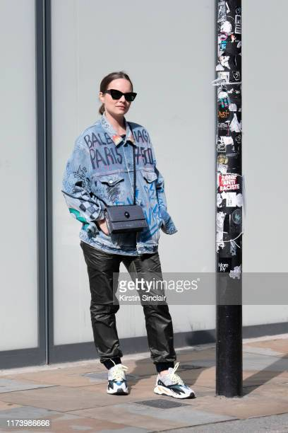 Alexandra Gorbounova wears a Balenciaga denim jacket vintage sunglasses colourful trainers a Kurt Geiger bag and black trousers on August 23 2019 in...