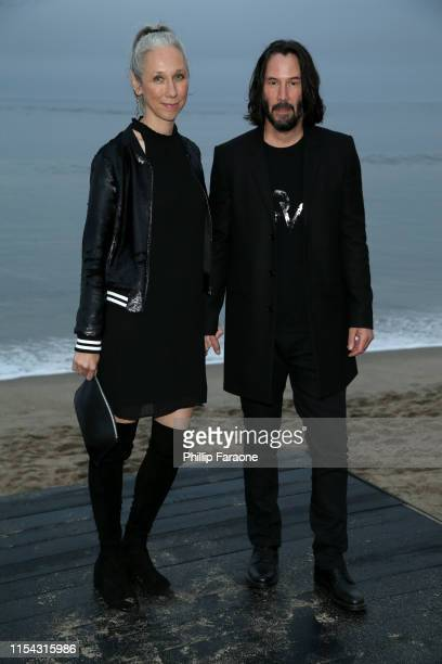 Alexandra Grant and Keanu Reeves attend the Saint Laurent Mens Spring Summer 20 Show on June 06 2019 in Malibu California