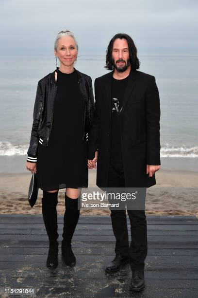 Alexandra Grant and Keanu Reeves attends the Saint Laurent Mens Spring Summer 20 Show on June 06 2019 in Paradise Cove Malibu California