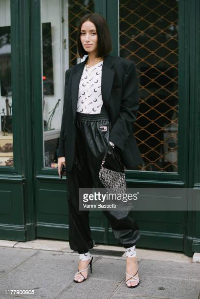 Alexandra Guerain poses wearing a Marine Serre X Nike jumpsuit and a Dior bag after the Thom Browne show at the Ecole des Beaux Arts during Paris...