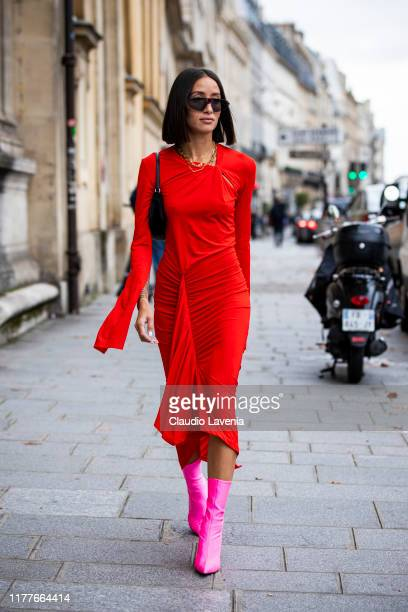 Alexandra Guerain, wearing a red midi dress and fuchsia boots, is seen outside the Unravel show during Paris Fashion Week - Womenswear Spring Summer...