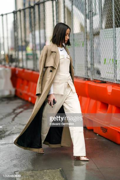 Alexandra Guerain wears a brown long trench coat, a Nike t-shirt, a corset, cream-color pants, during New York Fashion Week Fall Winter 2020, on...