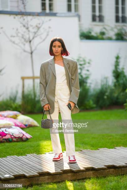 Alexandra Guerain wears a gray oversized blazer jacket, a white ribbed asymmetric top, white pants, a bejeweled bag, red Nike sneakers shoes, during...