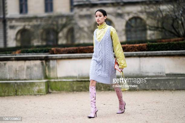Alexandra Guerain wears a pale blue wool dress, a yellow floral print top, pink boots, a yellow bag, outside Kenzo, during Paris Fashion Week -...