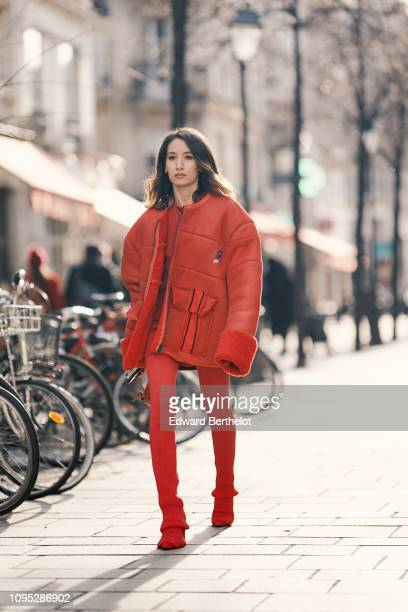 Alexandra Guerain wears a red leather aviator jacket with red wool inner lining a red dress red leggings over her shoes during Paris Fashion Week...