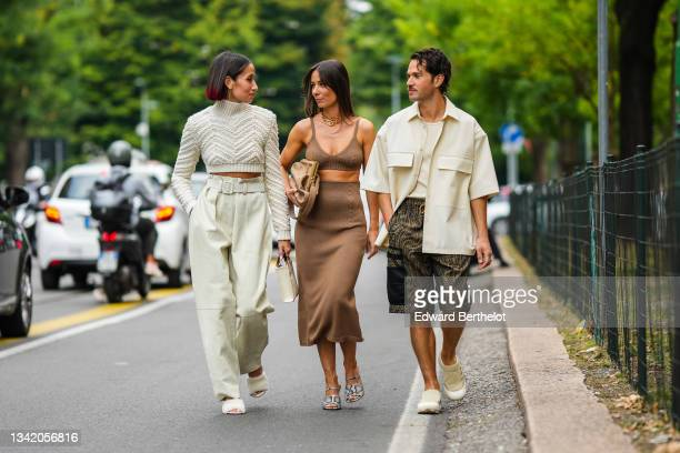 Alexandra Guerain wears a white latte braided wool turtleneck cropped pullover, beige belted ribbed large pants, a beige matte leather handbag from...