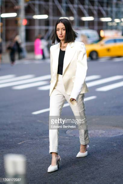 Alexandra Guerain wears a white oversized blazer jacket, a black top, a necklace, white pants, white pointy shoes, outside Zadig & Voltaire, during...