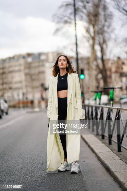 Alexandra Guerain wears earrings a creamcolor long coat an OffWhite black crop top black sport pants Hogan white sneakers outside Redemption during...