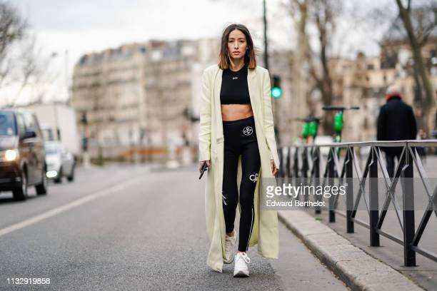 Alexandra Guerain wears earrings, a cream-color long coat, an Off-White black crop top, black sport pants with the logo Off, Hogan white sneakers,...