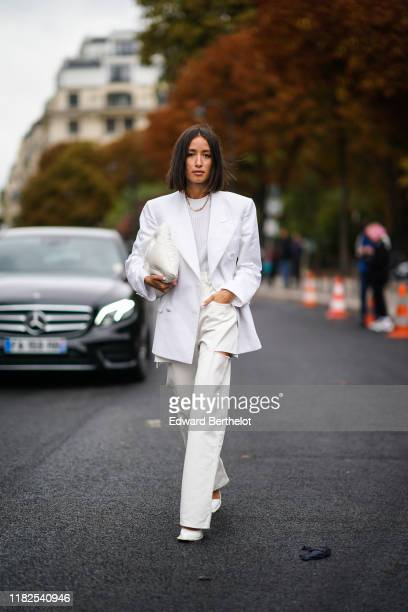 Alexandra Guerain wears earrings a necklace a white top a white jacket a white puff bag white ripped pants white shoes outside Margiela during Paris...