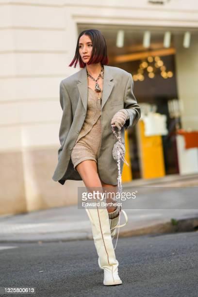 Alexandra Guerain wears metallic silver chain necklace with an animal-shaped pendant, a gray oversized long blazer jacket, a beige wool cardigan,...