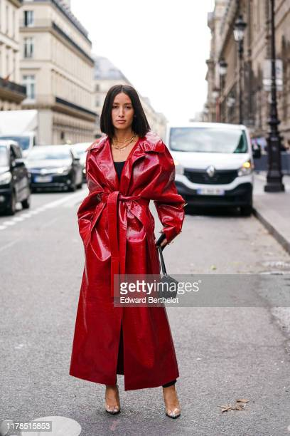 Alexandra Guerain wears necklaces a black top a shiny red vinyl trench coat with buttons at the cuffs transparent vinyl heeled slingback pumps a...