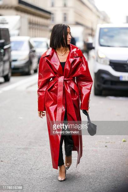 Alexandra Guerain wears necklaces a shiny red vinyl trench coat with buttons at the cuffs a black top black shiny vinyl pants transparent vinyl...