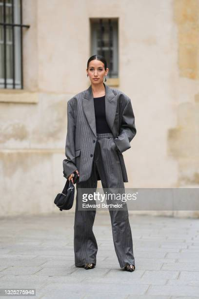 Alexandra Guerain wears silver and black Prada earrings, a black ribbed t-shirt, a gray striped oversized blazer jacket, gray striped matching large...