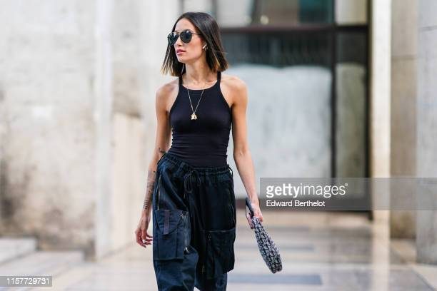 Alexandra Guerain wears sunglasses, a black tank top, large pants, a necklace, a Dior Saddle bag, outside Andrea Crews, during Paris Fashion Week -...