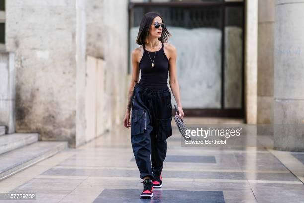 Alexandra Guerain wears sunglasses a black tank top large pants pink sneakers shoes a necklace a Dior Saddle bag outside Andrea Crews during Paris...
