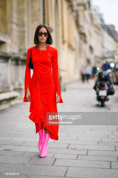 Alexandra Guerain wears sunglasses, necklaces, a black bag, a long sleeves gathered asymmetric red dress, neon-pink mid-calf sock-boots, outside...