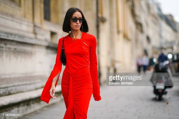 Alexandra Guerain wears sunglasses, necklaces, a black bag, a long sleeves gathered red dress, outside Unravel Project, during Paris Fashion Week -...