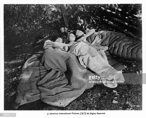 Alexandra Hay in the woods sleeping in between two men in a scene from the film '1000 Convicts And A Woman' 1971