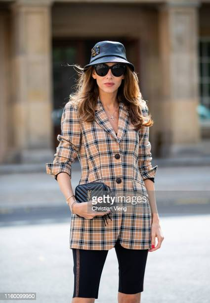 Alexandra Lapp is seen wearing a beige brown checkered blazer, black cycling pants and black bucket hat from Riani, black St. Laurent Lou belt bag...