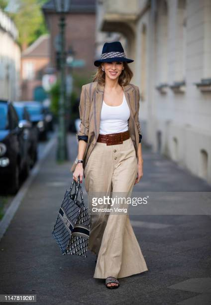 Alexandra Lapp is seen wearing a beige brown long striped blazer from Zara, white tank top from H&M, waisted belt from Max Mara, high waisted wide...