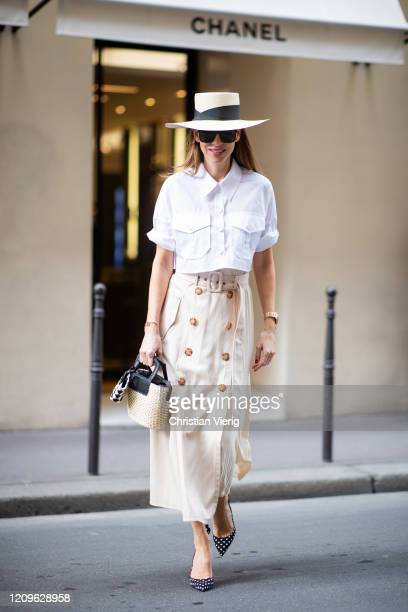 Alexandra Lapp is seen wearing a beige pleated skirt by Riani white short blouse from Riani straw hat and straw bag from Sensi Studio micro Bottega...