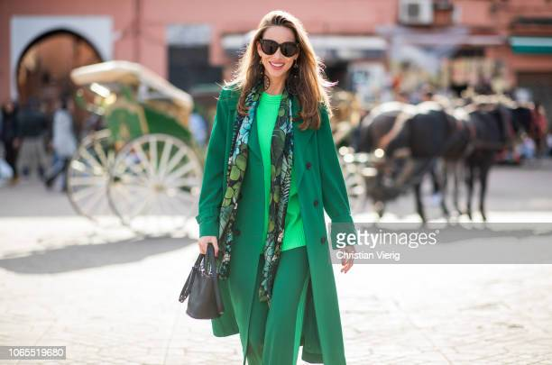 Alexandra Lapp is seen wearing a belted long crepe Marc Cain coat in green a neon green sweater and crepe loosefit pants with stripes in two green...