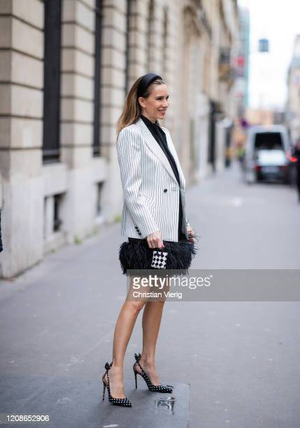 Alexandra Lapp is seen wearing a black 16Arlington black dress with feathers, Blazé Milano black and white striped blazer, micro mini bag from...