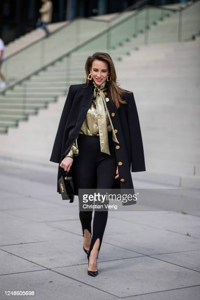Alexandra Lapp is seen wearing a black Balenciaga oversized-dress worn as a coat with big shoulder pads and golden buttons, Saint Laurent stretch...