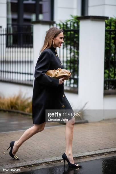 Alexandra Lapp is seen wearing a black Balenciaga oversized-dress worn as a coat with big shoulder pads and golden buttons, brown Bottega Veneta The...
