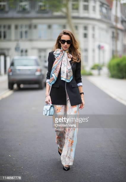 Alexandra Lapp is seen wearing a black blazer with flower printed wide leg pants, a printed foulard, a small light blue bag and black pumps - all...
