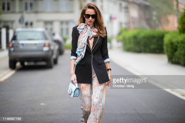 Alexandra Lapp is seen wearing a black blazer with flower printed wide leg pants, a printed foulard, a small light blue bag - all from Marc Cain and...
