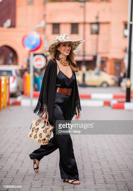 Alexandra Lapp is seen wearing a black satin jumpsuit with a wide leg from HM a loose wide black jacket with fringes from Zara a Panama hat with a...