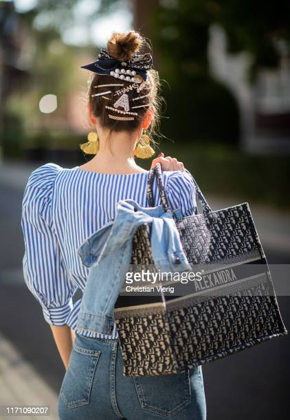 Alexandra Lapp is seen wearing a blue Dior Book Tote Dior Oblique, Goldsign blue jeans, a blue and white striped wrap blouse from Zara, blue...