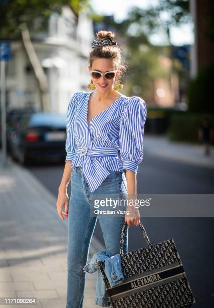Alexandra Lapp is seen wearing a blue Dior Book Tote Dior Oblique, Goldsign blue jeans, a blue and white striped wrap blouse from Zara, Dior Oblique...