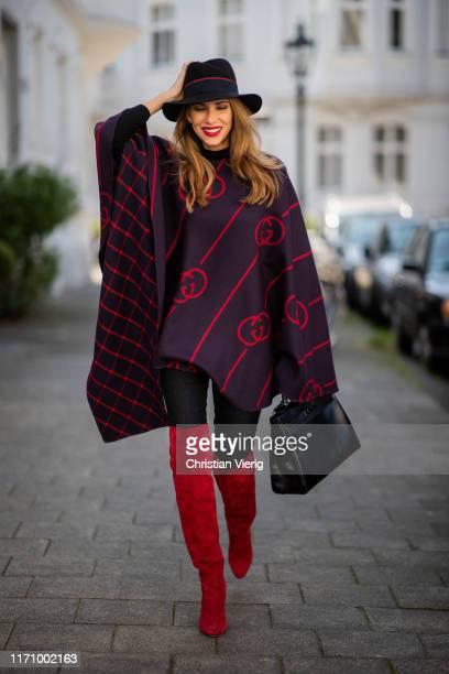 Alexandra Lapp is seen wearing a blue red Gucci cape, Hermès So Black Kelly bag, black Maison Michel Fedora Virginie felt hat, red suede Gianvito...