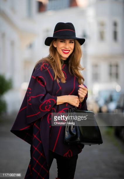 Alexandra Lapp is seen wearing a blue red Gucci cape, Hermès So Black Kelly bag, black Maison Michel Fedora Virginie felt hat, black Marc Cain...