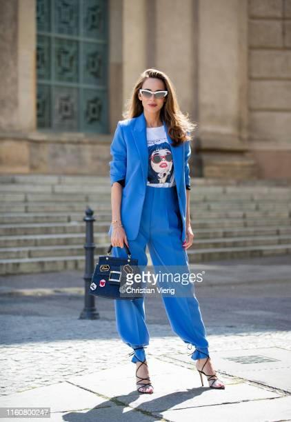 Alexandra Lapp is seen wearing a blue Zara suit, white Re/Done print T-shirt, blue Roger Vivier denim Viv' bag, white miu miu cat-eye shaped...