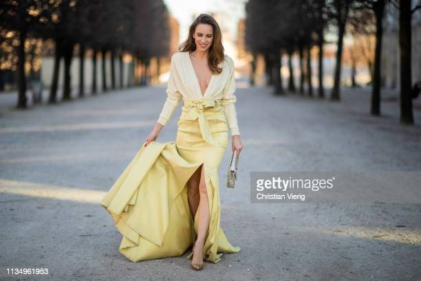 Alexandra Lapp is seen wearing a combination from Talbot Runhof made up of a long high-waist belted yellow skirt with a cut out up front and glitter...