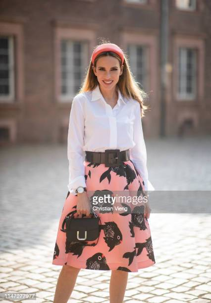 Alexandra Lapp is seen wearing a flared CloquéJacquardskirt in pink with a blowfish print a white blouse a waist belt in black a little black handbag...