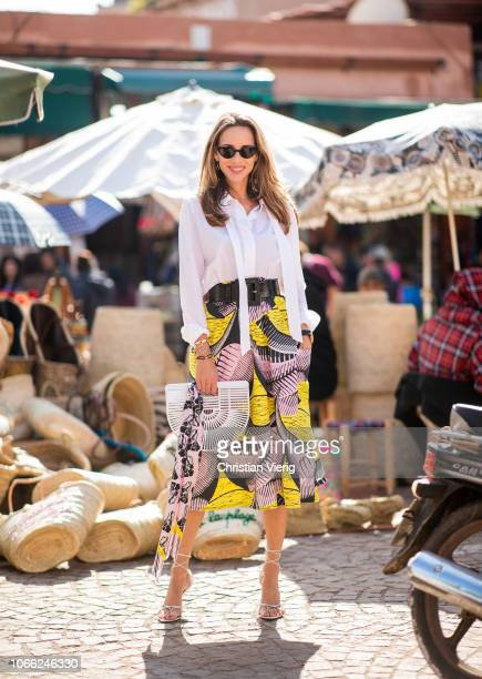 Alexandra Lapp is seen wearing a flared skirt printed with pink yellow and black patterns combined with a plain bowed white shirt a matching silk...