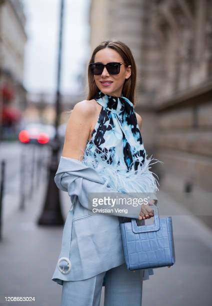 Alexandra Lapp is seen wearing a light blue De La Vali suit blue Shirley mini bag from Staud 16Arlington satin top with feathers squareframe black...