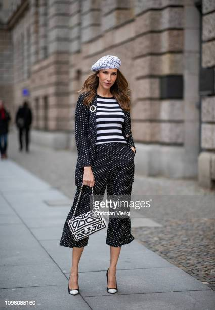 Alexandra Lapp is seen wearing a long black blazer with dots and matching culotte pants black and white striped sweater with a yellow detail from...