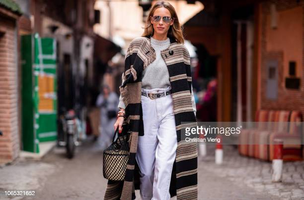 Alexandra Lapp is seen wearing a long Huan fringed striped wool cape from Isabel Marant an oversized grey wool sweater from HM white highrise...